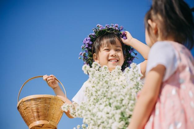 Bambini belli e allegri che giocano insieme nel giardino di fiori bianchi Foto Premium