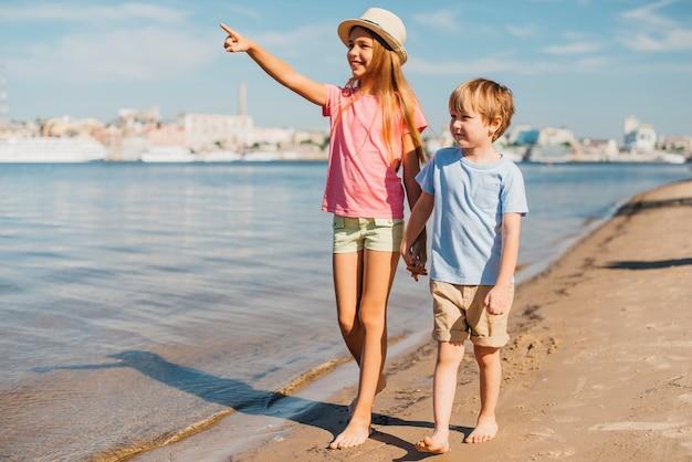 Bambini che camminano lungo la spiaggia Foto Gratuite