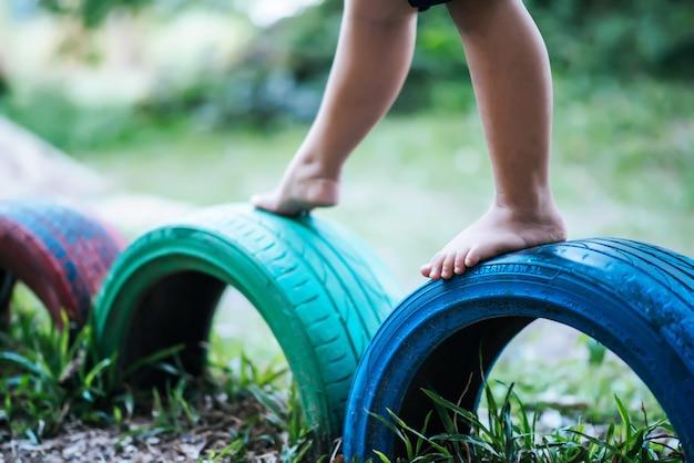 Disegno Di Bambino Che Corre : Bambini che corrono con le gomme nel parco giochi. scaricare foto