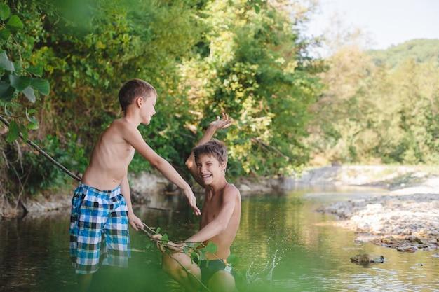 Bambini che giocano e spruzzi nel fiume Foto Premium