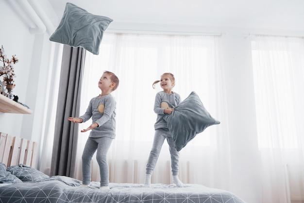 Bambini che giocano nel letto dei genitori. i bambini si svegliano nella soleggiata camera da letto bianca. ragazzo e ragazza giocano in pigiama coordinato. indumenti da notte e biancheria da letto per bambini e neonati. interno della scuola materna per bambino. famiglia mattina Foto Premium