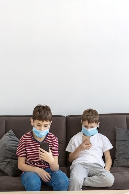 Bambini che giocano su smartphone mentre indossano maschere mediche Foto Gratuite