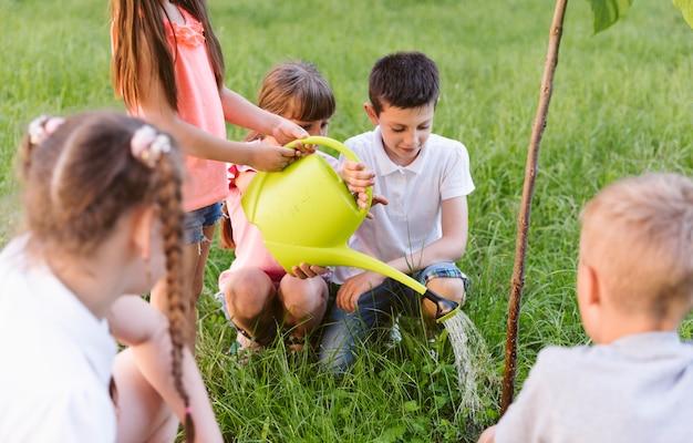 Bambini che placcano e annaffiano l'albero Foto Gratuite