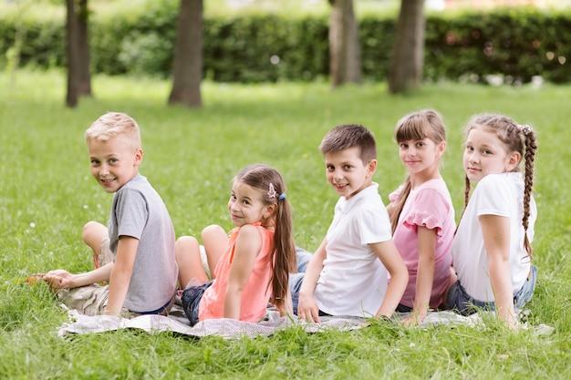 Bambini che posano sulla coperta fuori Foto Gratuite