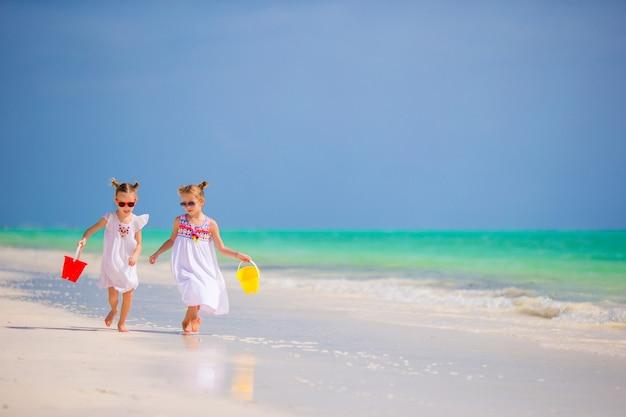 Bambini che si divertono in spiaggia tropicale giocando insieme in acque poco profonde Foto Premium
