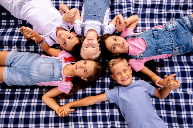 Bambini che si trovano sulla coperta che tiene a mano Foto Gratuite