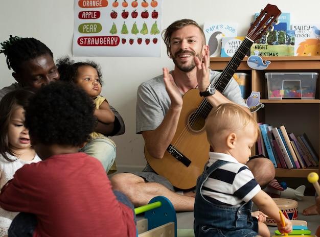 Bambini della scuola materna che giocano con gli strumenti musicali nell'aula Foto Premium