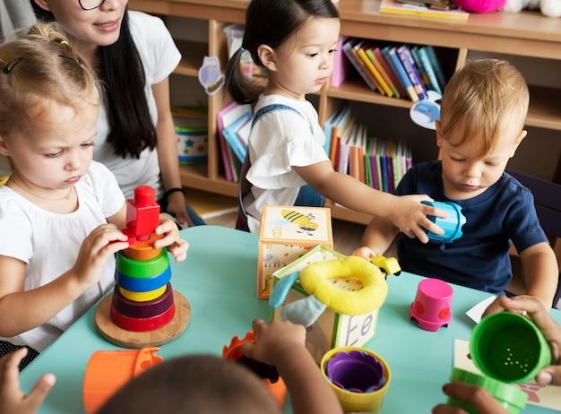 Bambini della scuola materna che giocano con l'insegnante nell'aula Foto Premium