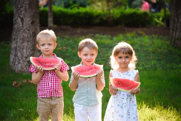 Bambini divertenti che mangiano anguria all'aperto nel parco di estate. Foto Premium