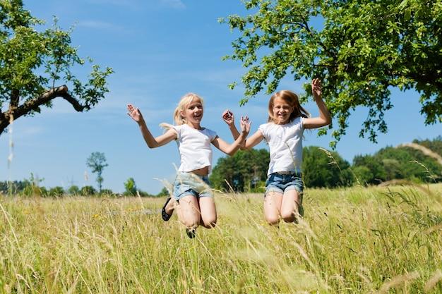 Bambini felici che saltano in un prato soleggiato Foto Premium