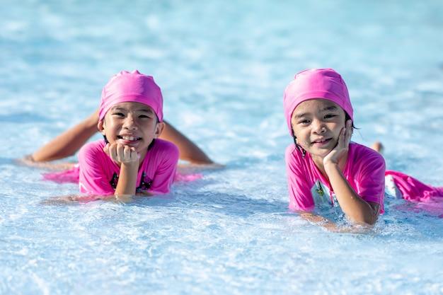 Bambini felici che smilling sul parco acquatico in piscina Foto Premium