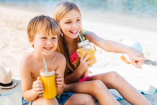 Bambini felici che sorridono con la bevanda sulla costa Foto Gratuite