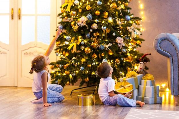 Bambini felici in pigiama guardando l'albero di natale nel bellissimo soggiorno Foto Premium