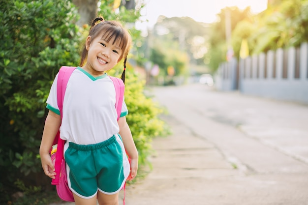 Bambini felici in tuta da studente e borsa pronta per andare a scuola per l'apprendimento Foto Premium