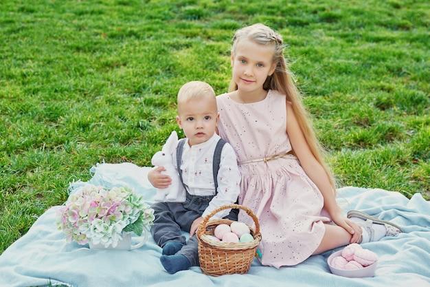 Bambini nel parco il picnic di pasqua con uova e coniglio Foto Premium