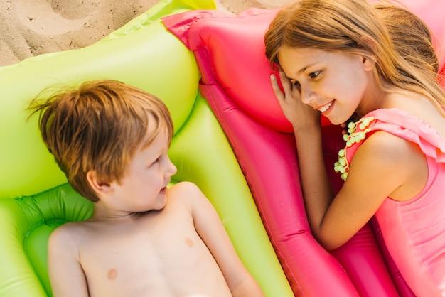 Bambini piccoli che riposa su materassi gonfiati sulla spiaggia Foto Gratuite