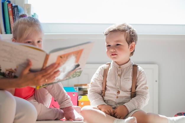 Bambini seduti guardando libro Foto Gratuite