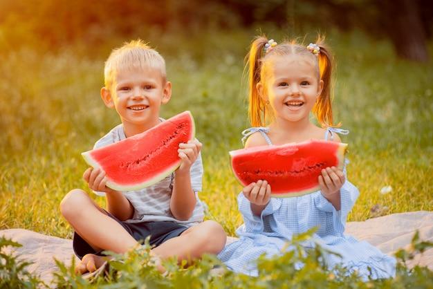 Bambini sul prato con fettine di anguria nelle loro mani nei raggi del tramonto Foto Premium