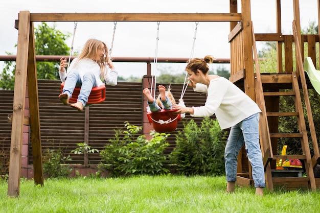 Bambini sull'altalena. sorelle delle ragazze che oscillano su un'oscillazione nel cortile. divertimento estivo. Foto Gratuite