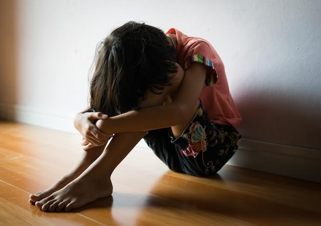 Bambini tristi, ragazza che si siede da solo nell'angolo a casa Foto Premium