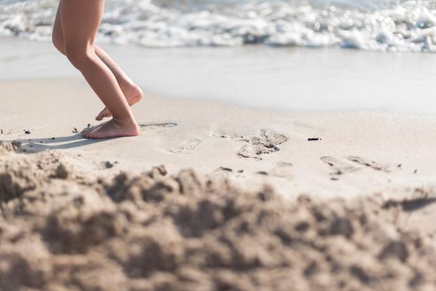 Bambino a piedi nudi che gioca in riva al mare Foto Gratuite