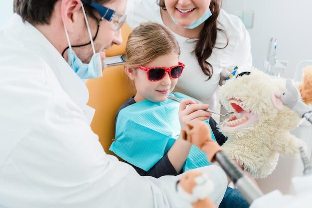 Bambino all'ufficio del dentista che si occupa dei denti del giocattolo dell'animale domestico Foto Premium