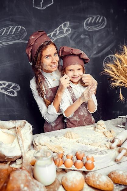 Bambino allegro con la madre che produce pasta Foto Premium