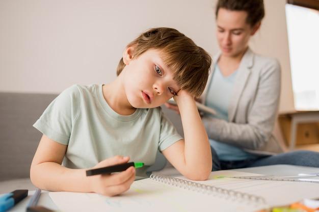 Bambino annoiato a casa mentre viene istruito Foto Gratuite