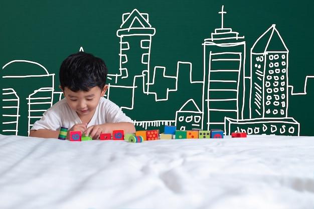 Bambino asiatico che gioca giocattolo con il disegno di architettura della costruzione, disegnato a mano Foto Premium