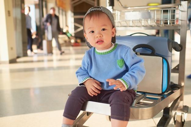 Bambino asiatico sveglio del ragazzo del bambino di 2 anni con la valigia, sedentesi sul carrello all'aeroporto, viaggio della famiglia & vacanza con il concetto del bambino Foto Premium