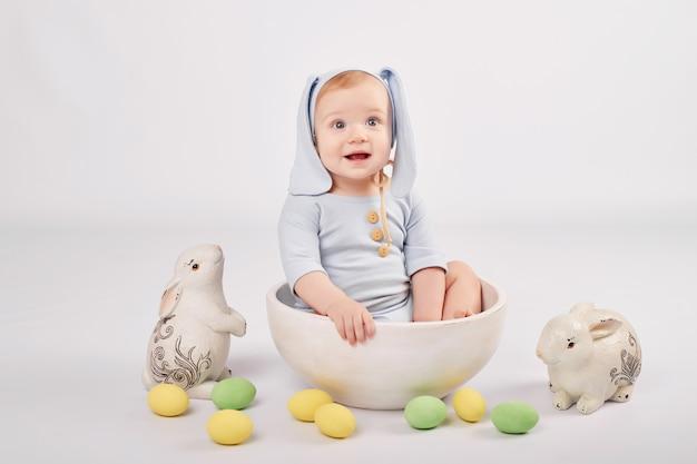 Bambino carino con coniglietti e uova di pasqua dipinte Foto Premium