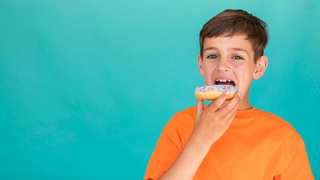 Bambino che mangia una ciambella con spazio di copia Foto Gratuite