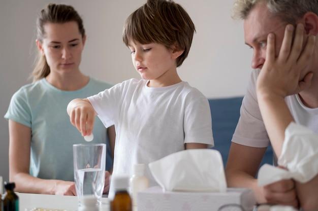 Bambino che mette una pillola in un bicchiere d'acqua Foto Gratuite