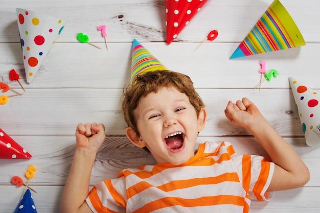 Bambino che ride che si trova sul pavimento di legno con cappello di partito di carnevale. Foto Premium
