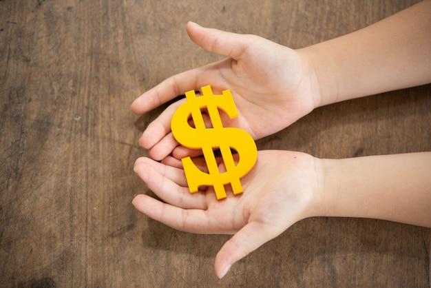 Bambino che tiene il simbolo di dollaro giallo Foto Gratuite