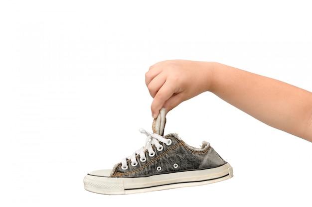 Bambino che tiene una vecchia sneaker sporca e puzzolente Foto Premium