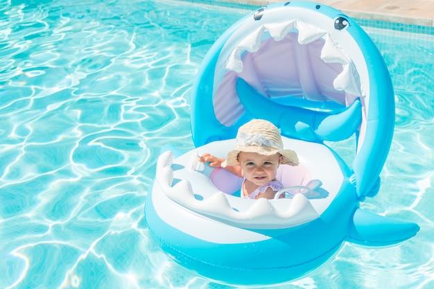 Bambino con cappello su un galleggiante a forma di squalo in piscina Foto Premium