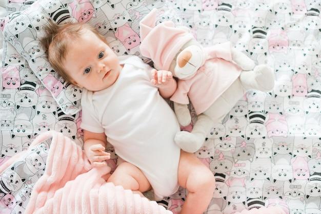 Bambino con giocattolo sdraiato sul letto Foto Gratuite