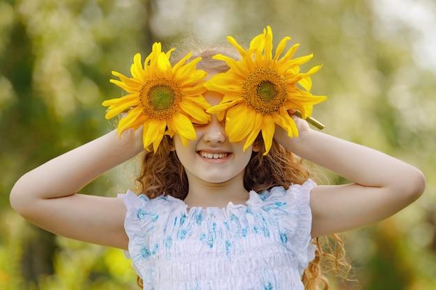 Bambino con i girasoli in mano mostra denti bianchi; godersi la natura in una giornata di sole estivo. Foto Premium