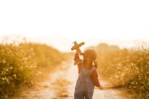 Bambino con l'aeroplano giocattolo in natura al tramonto Foto Premium