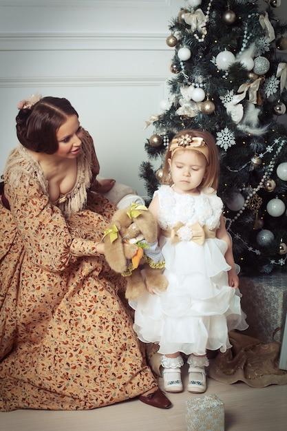 Bambino con la madre che riceve vicino all'albero di natale. Foto Premium