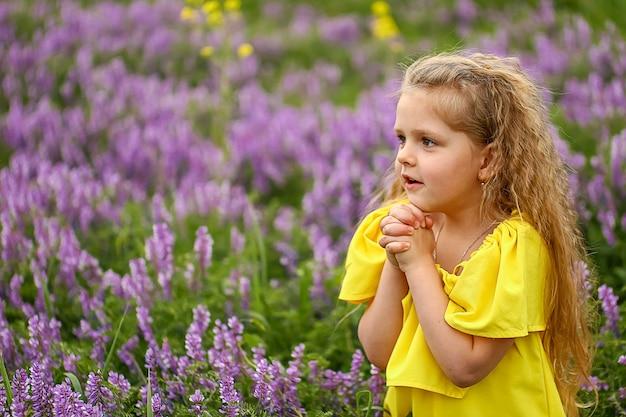 Bambino con riccioli in un campo di lavanda, vestito con un prendisole giallo, sera d'estate Foto Premium