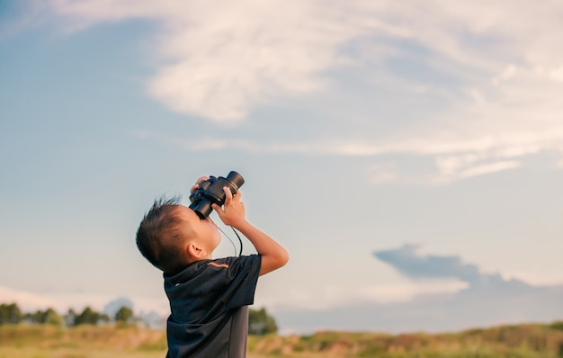 Bambino con un binocolo guardando il cielo scaricare