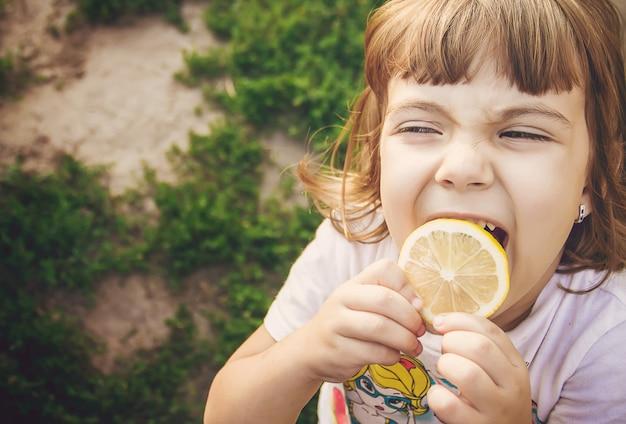 Bambino con un limone messa a fuoco selettiva cibo e bevande. Foto Premium
