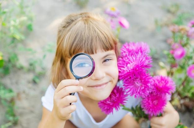Bambino con una lente d'ingrandimento in mano. Foto Premium