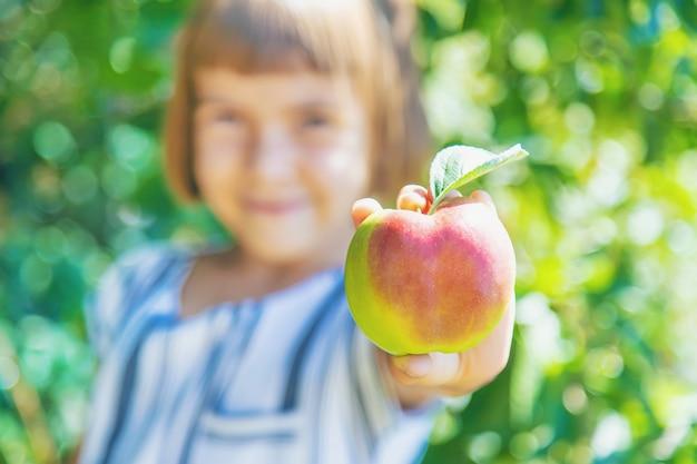 Bambino con una mela in giardino Foto Premium