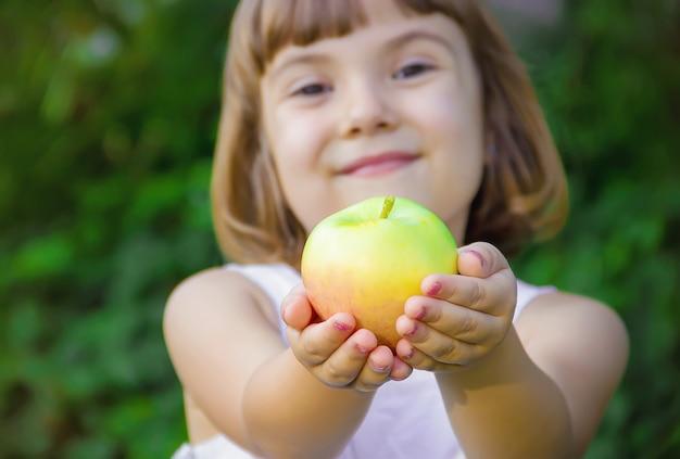 Bambino con una mela messa a fuoco selettiva natura Foto Premium