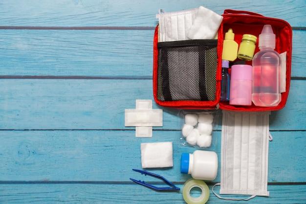 Bambino di borsa di pronto soccorso vista dall'alto con forniture mediche su legno Foto Premium