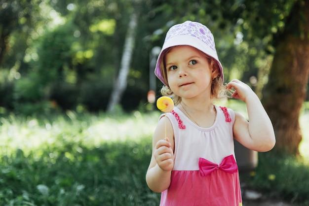 Bambino divertente con la lecca-lecca della caramella, bambina felice che mangia grande Foto Premium