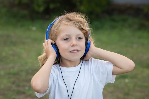 Bambino divertente con musica d'ascolto dei capelli lunghi con hadphone blu Foto Premium